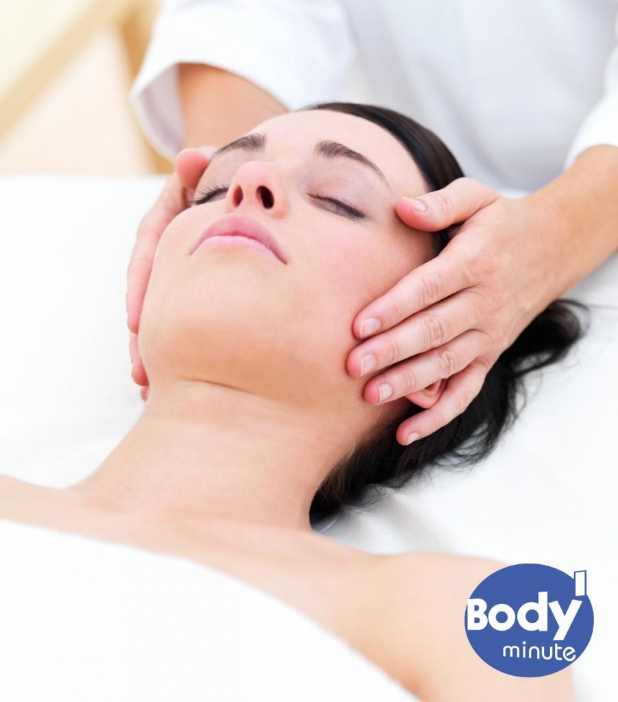 Beautiful young lady receiving facial massage at day spa