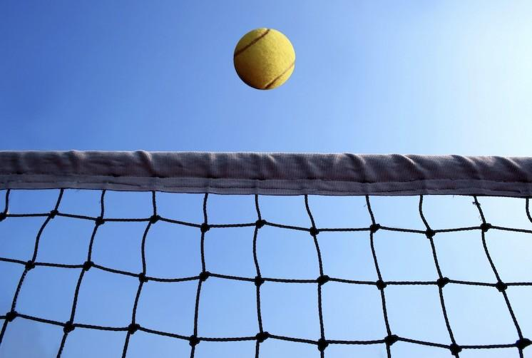 filet de tennis et une balle devant un ciel bleu