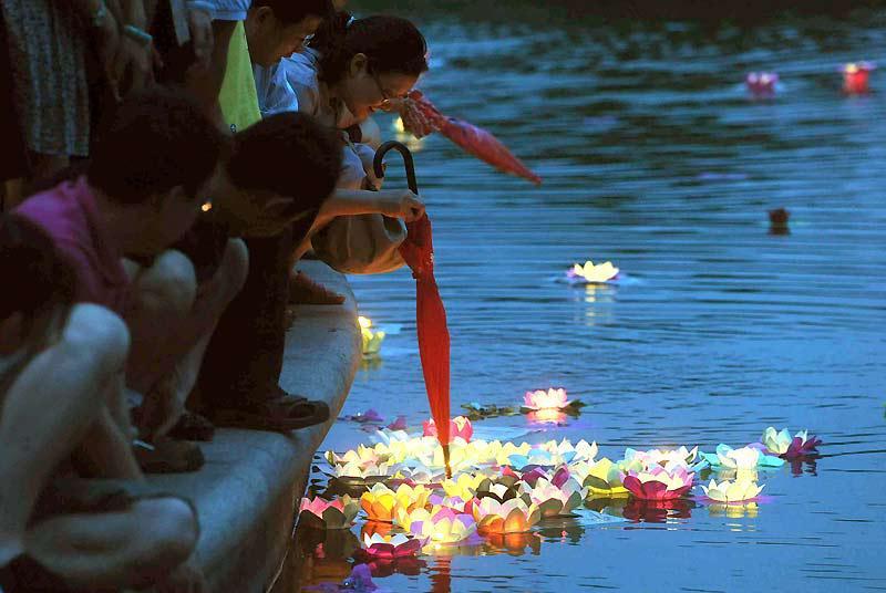 Mercredi 16 juin, ces familles chinoises déposent, sur un lac, des lanternes flottantes confectionnées avec des fleurs de lotus, pour marquer le début du festival de Duanwu, également connu sous le nom de Dragon Boat Festival.