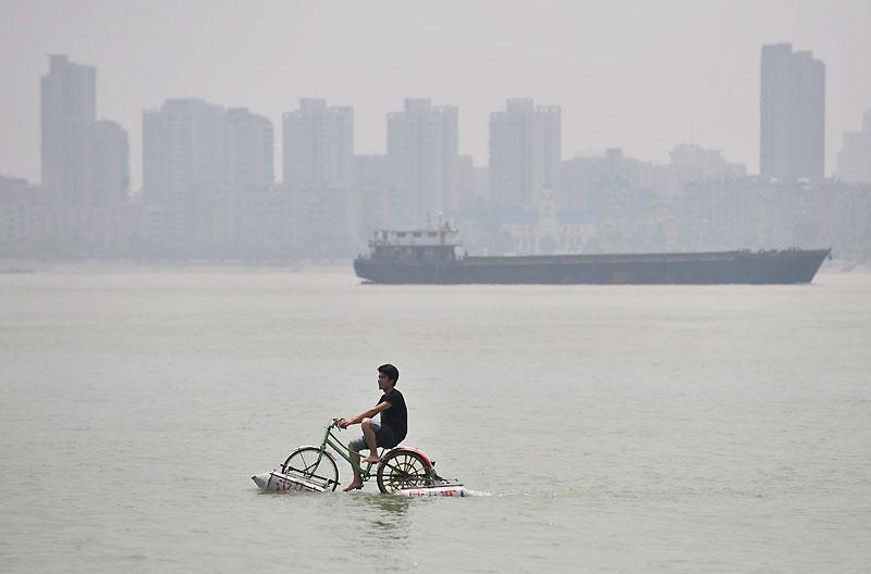 Cet homme se déplace avec un vélo flottant sur le fleuve qui traverse Wuhan, dans la province de Hubei, en Chine, mercredi 16 juin.