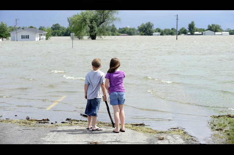 <b></div>En crue</b>. On en a tous rêvé. Enfin, loin du regard de leurs parents, ils peuvent mettre les pieds dans cette énorme flaque. Sur cette photo, prise mardi 21 juin, dans la région de Corning, dans le Missouri, le fleuve du même nom, en crue, n'en finit pas de provoquer de fulgurantes inondations. En débordant de ses digues, plus de 1000 hectares de terres agricoles ont été totalement envahies par les eaux et des centaines de personnes ont dû fuir leurs habitations. Selon les experts, la décrue devrait s'amorcer lentement ces prochains jours. Mais pour les sinistrés, le retour à la normale pourrait prendre plusieurs semaines.