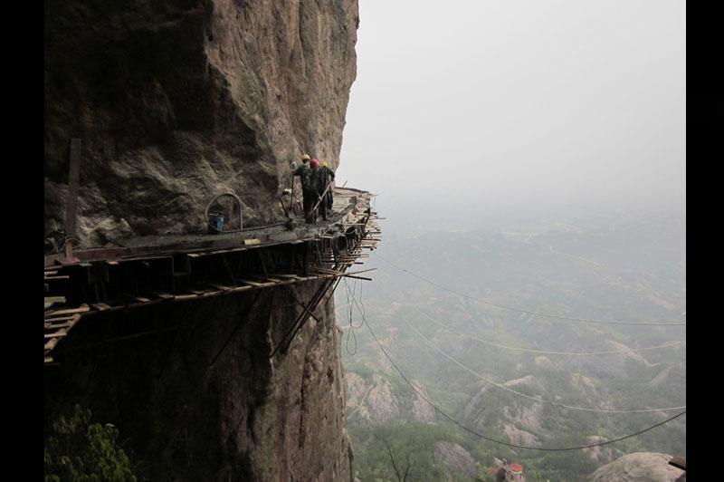 <b></div>Travaux glissants</b>. Le sentier panoramique en bois que ces ouvriers sont entrain de construire sera bientôt le plus long (3 km) et le plus vertigineux (plus de 1 000mde hauteur, sur moins d'1 m de large) de Chine. Un travail effroyablement dangereux qu'ils effectuent sans être encordés et sous la mousson, au flanc d'une falaise totalement lisse. Personne ne sait combien ils sont payés ni combien d'entre eux sont peut-être déjà tombés, mais quand on leur demande ce qui est le plus dur, ils répondent que la partie la plus risquée (planter les premiers pitons) est derrière eux et que le plus difficile: «C'est surtout de rester plusieurs mois dans ces montagnes, sans jamais rentrer chez soi.»