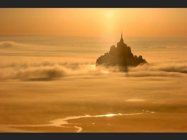 Le Mont-Saint-Michel se détache dans la brume orangée, en Normandie (France).