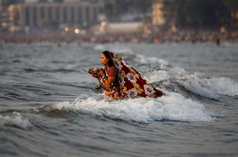 <b></div>Offrande au soleil.</b> Les muscles tétanisés pour mieux résister aux flots de la mer d'Oman, au pied de la ville indienne de Mumbai (Bombay), cette femme va rester en prière de longues heures, psalmodiant des poèmes rituels en l'honneur de l'astre solaire, à l'occasion d'une des plus importantes fêtes religieuses du calendrier hindou : le festival du Chhath. Chaque année, une foule immense se précipite au bord de la mer ou sur les rives du Gange pour adorer le Soleil et tenter d'attirer sa bénédiction. Un rite dont les racines plongent dans les plus anciennes croyances humaines. Dans la cosmogonie de l'hindouisme, le dieu Soleil doit être remercié pour sa lumière et sa chaleur, garante de la vie sur Terre.