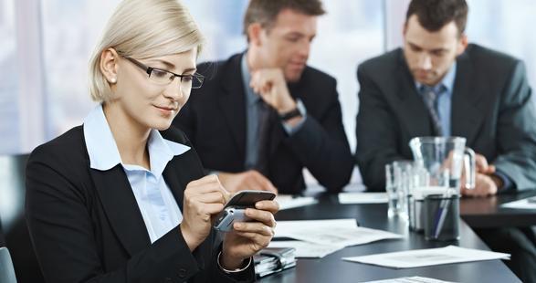 professionnels en salle de réunion avec des appareils mobiles