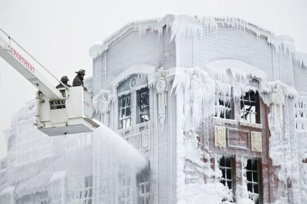 Firefighters spray down hot spots on an ice covered warehouse that caught fire Tuesday night in Chicago