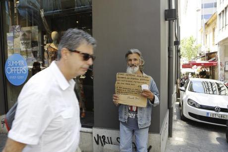 Un cadre d'entreprise passe devant un clochard dans les rues d'Athênes