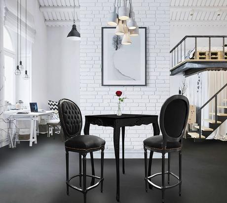 mur en briques blanche et béton ciré au sol associés à une table de bar et deux chaises de bar Royal Art Palace