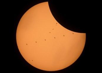 La Lune passe devant le Soleil et à cet instant, encore plus près de nous, la Station spatiale internationale passe aussi. La silhouette d'ISS épaulée de ses immenses panneaux solaires se distingue des taches solaires aux contours moins nets. Au même moment, les astronautes à bord de la Station voient une tache sombre glisser sur la Terre… — Crédit : NASA, Joel Kowsky
