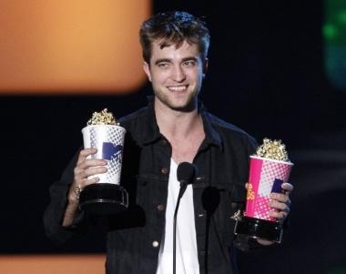 Actor Robert Pattinson accepts awards for Best Male Performance and for Global Superstar at the 2010 MTV Movie Awards in Los Angeles, June 6, 2010. REUTERS/Mario Anzuoni (UNITED STATES - Tags: ENTERTAINMENT IMAGES OF THE DAY)