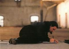 lying on warehouse floor, writing, close-up–'U2 Rattle & Hum - The official book of the U2 movie'–[home8.inet.tele.dk].jpg