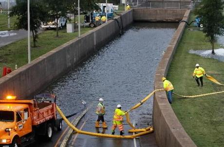 Virginia Dept. of Transportation workers place hose to pump out floodwater at the entrance of Mid...
