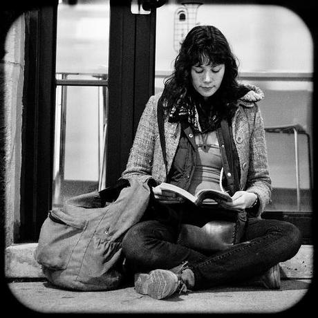 Girl reading at the bus stop