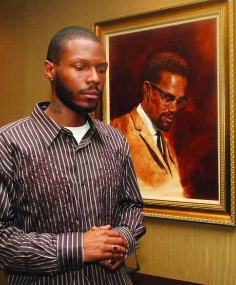MALCOLM SHABAZZ pose devant un portrait de son grand père Malcolm X
