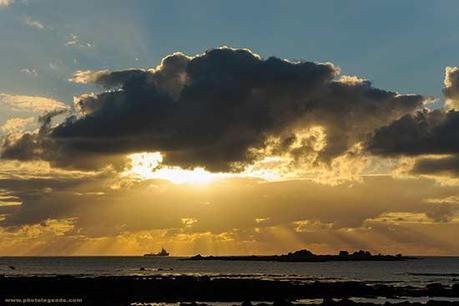 Un bateau s'approche du port de Saint Génolé sous les rayons du soleil