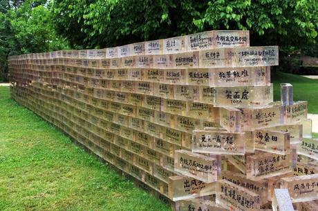 oeuvre d'art de shu yong représentant un mur de briques en resine transparentes avec des bulles d'air dans la résine et des inscription en chinois et anglais