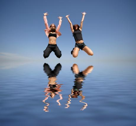 two girl jumping to the water