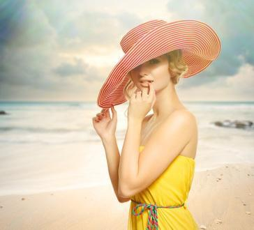 Beautiful girl in a hat enjoying the sun on the beach.
