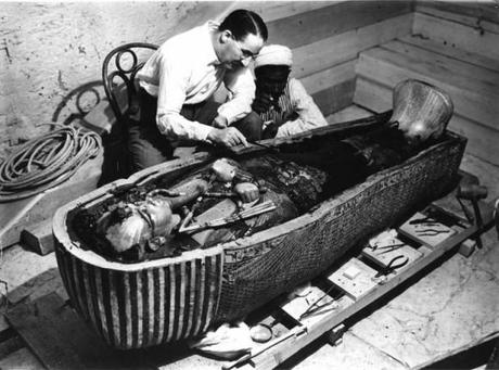 Howard Carter examining coffin of Tutankhamen which he discovered inside intact tomb of 14th century Egyptian pharoah, 1922