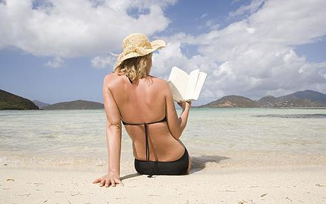 Woman on beach reading book, rear view