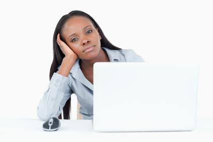 Bored businesswoman using a laptop against a white background