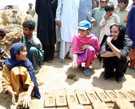 Hollywood actress and Oscar winner, Angelina Jolie (R), who is also the United Nations High Commissioner for Refugees (UNHCR) Goodwill Ambassador, looks at an Afghan refugee making bricks at a bricks kiln in the outskirts of Islamabad May 6, 2005. Jolie asked on Saturday for increased international help to repatriate more than 3 million Afghans living in Pakistan. Picture taken May 6, 2005. REUTERS/UNHCR/handout PAKISTAN REFUGEES JOLIE