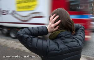The illustration shows a woman holds her ears as a lorry drives by in busy traffic in Hamburg, Germany, 11 January 2013. Photo: Axel Heimken