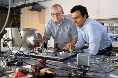 Photograph of Peter McMahon and Alireza Marandi with the Stanford Ising machine