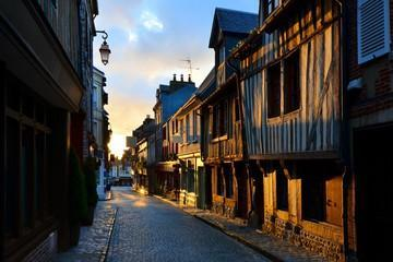 Picturesque street in the Normandy town of Honfleur, France with light of the rising sun
