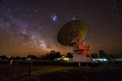 Photograph showing the Large (centre left) and Small (centre right) Magellanic Clouds in the sky above the Australia Telescope Compact Array