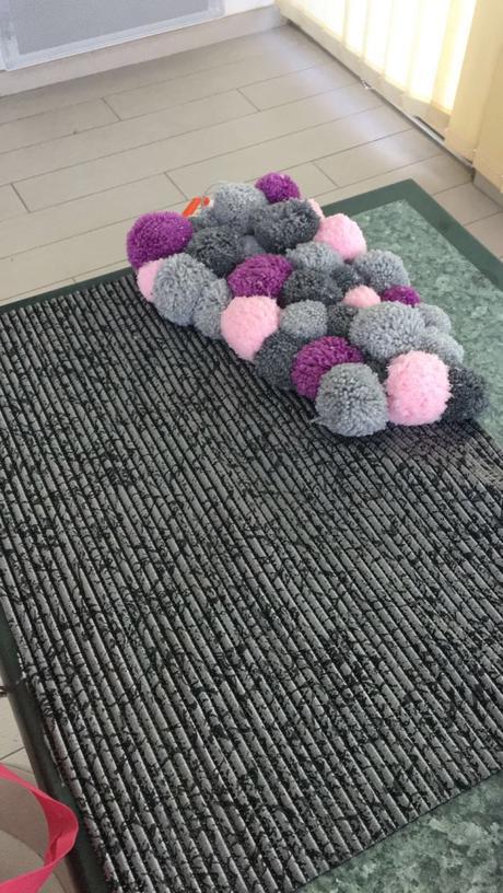 Un tapis en pompons de laine pour nos douces soirées d'hiver