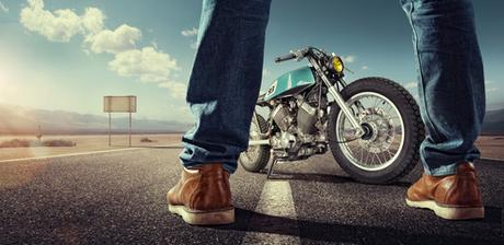 Sport. Biker standing near the motorcycle on an empty road at sunny day. Close view on legs_92850548_XS