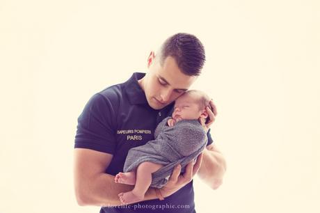 bébé dans les bras de son papa pompier