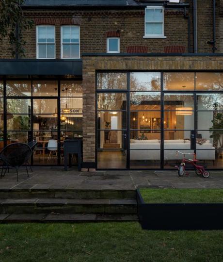 maison ouverte jardin terasse vue interieur baies vitrees briques exterieur canape salon cuisine jardin terasse
