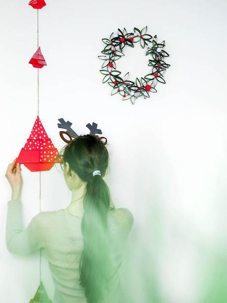 bricolage de noel enfant qui accroche ses décorations guirlande de noel couronne de papier