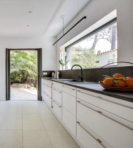 cuisine fermée meuble blanc robinet noir ouverture extérieure plan de travail noir clematc