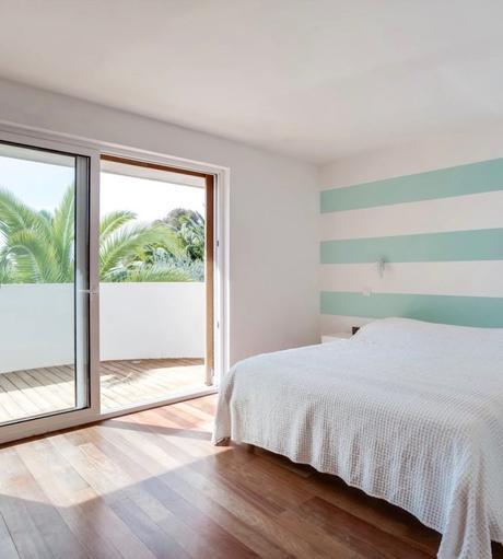chambre avec balcon baie vitrée lit parquet bois mur bleu marinière clemaroundthecorner