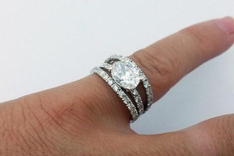 large bague de fiancailles diamant passée au doigt