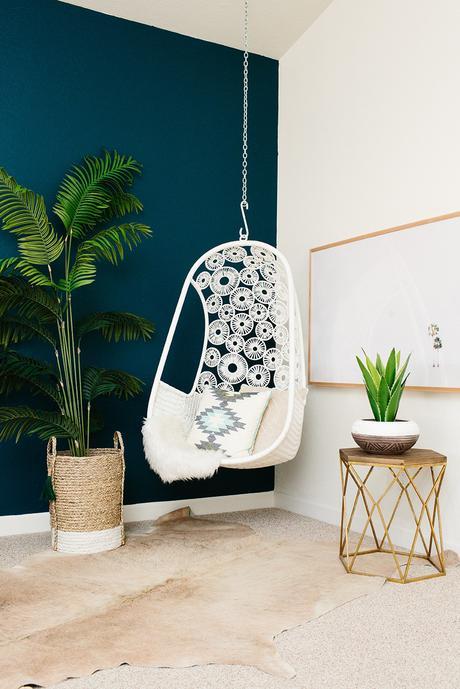 salon bohémien fauteuil en suspension plante verte mur bleu clematc
