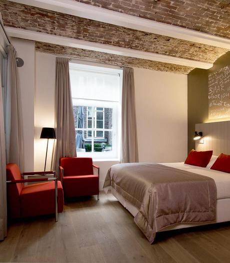 hôtel prison chambre rustique taupe plafond briques rouges clemaroundhtecorner