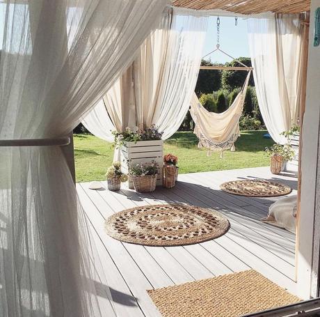 extérieur bohème chic voile rideau blanc tapis rond osier terrasse en bois hamac à pompon