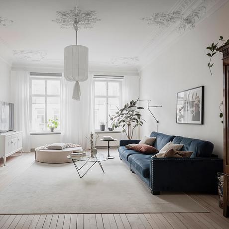 salon spacieux parquet en bois clair canapé bleu velours table basse verre pied métallique noire