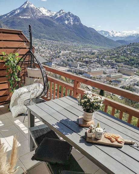 balcon table bois noir fauteuil suspendu rotin coussin lin - blog déco - clematc