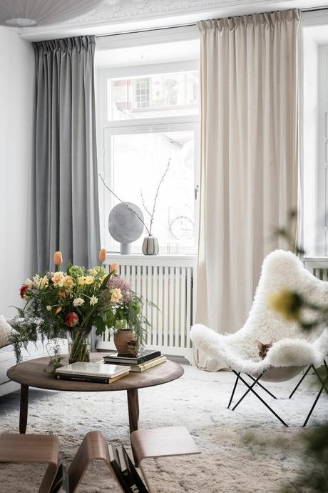 salon blanc table basse bois foncé rideaux gris foncé rose fauteuil papillon moumoutte