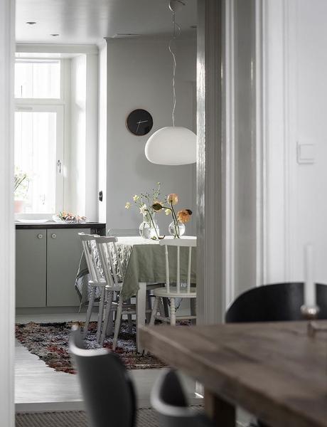 cuisine verte claire ouverte sur salon blanc nappe lin lavé