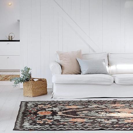 salon maison vacances déco blanche canapé lin tapis kilim motif floral noir