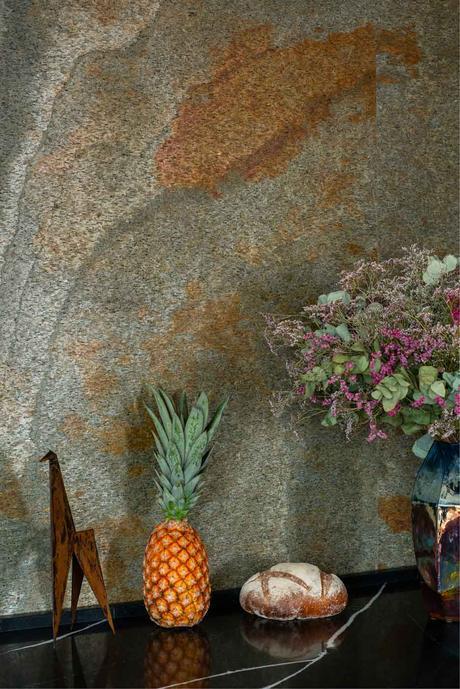 plan de travail noir effet marbre corian cosentino mur pierre verte orange reflet cuisine originale