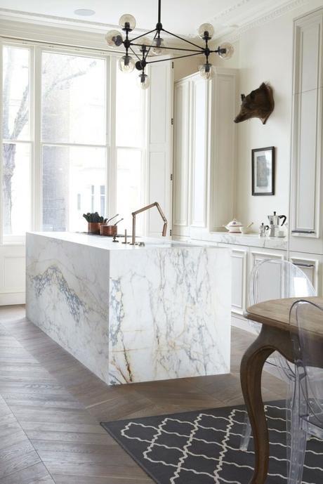 cuisine ouverte ilot central marbre chaises rondes transparentes tapis noir et blanc géométrique