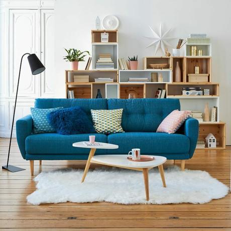 salon scandinave canapé bleu canard pieds en bois moulures aux murs tapis en fourrure blanche
