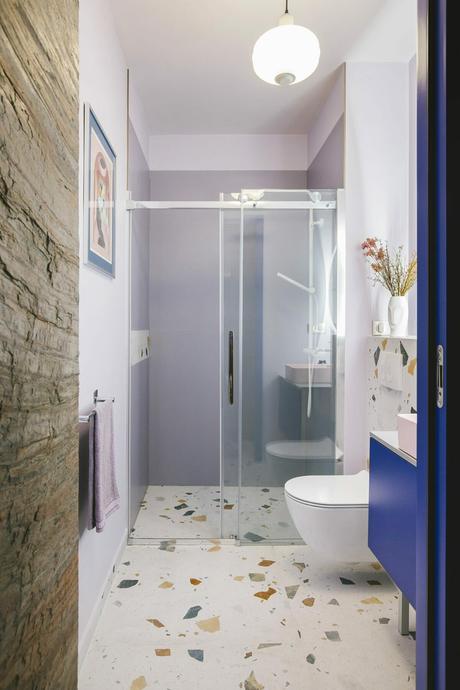 salle de douche italienne sol terrazzo grès cérame vase visage fleur séchée porte coulissante mur